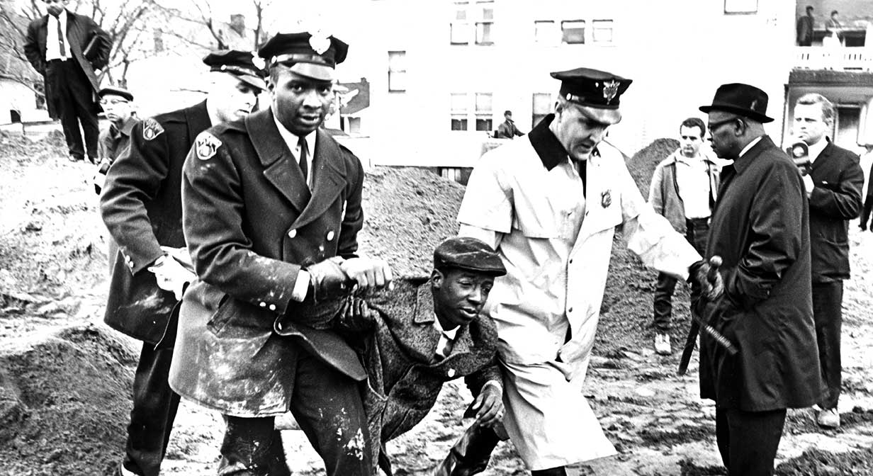 Police carry away a black protester at the at the Lakeview Rd. school construction site, 1964-04-07