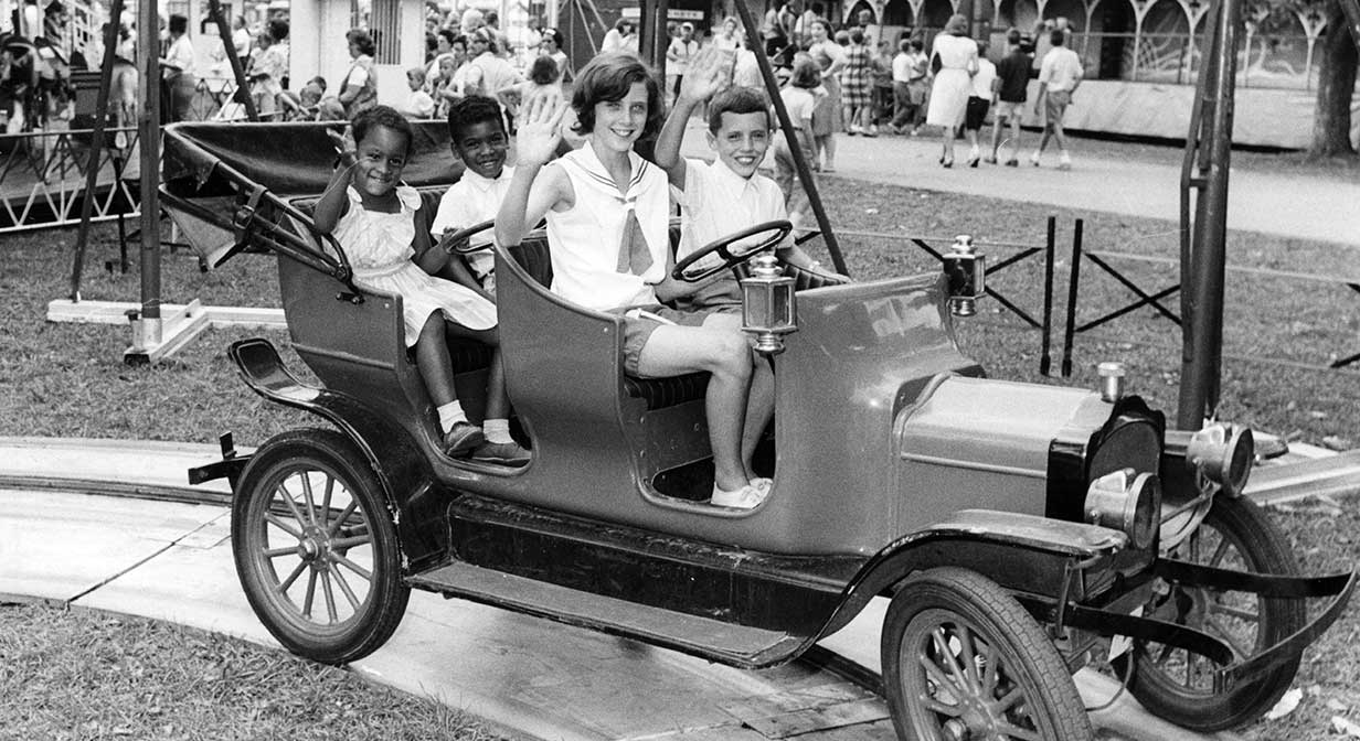 Children aboard an antique auto at the county fair