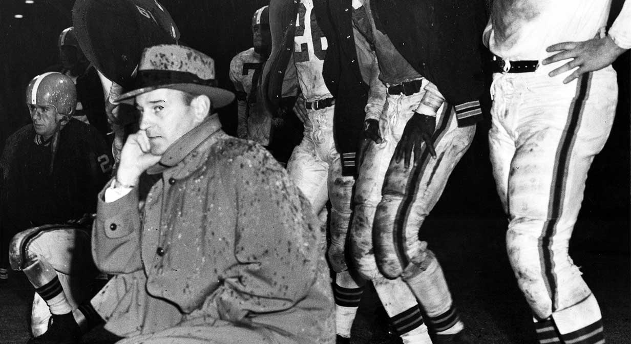 Paul Brown and players on sideline in the rain.