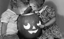 Two children looking into jack-o-lantern, 1938.