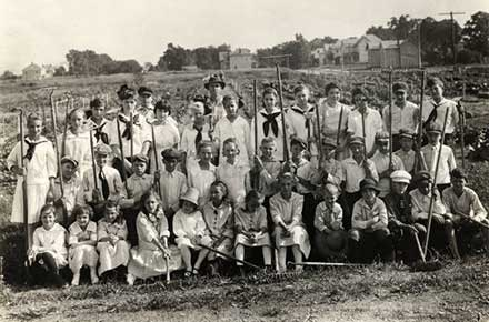 Group of student gardeners with tools, some dressed in sailor or midi shirts.