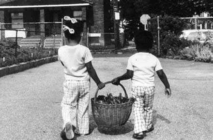 Two girls carry a basket of garden greens home from the school garden in Cleveland, Ohio
